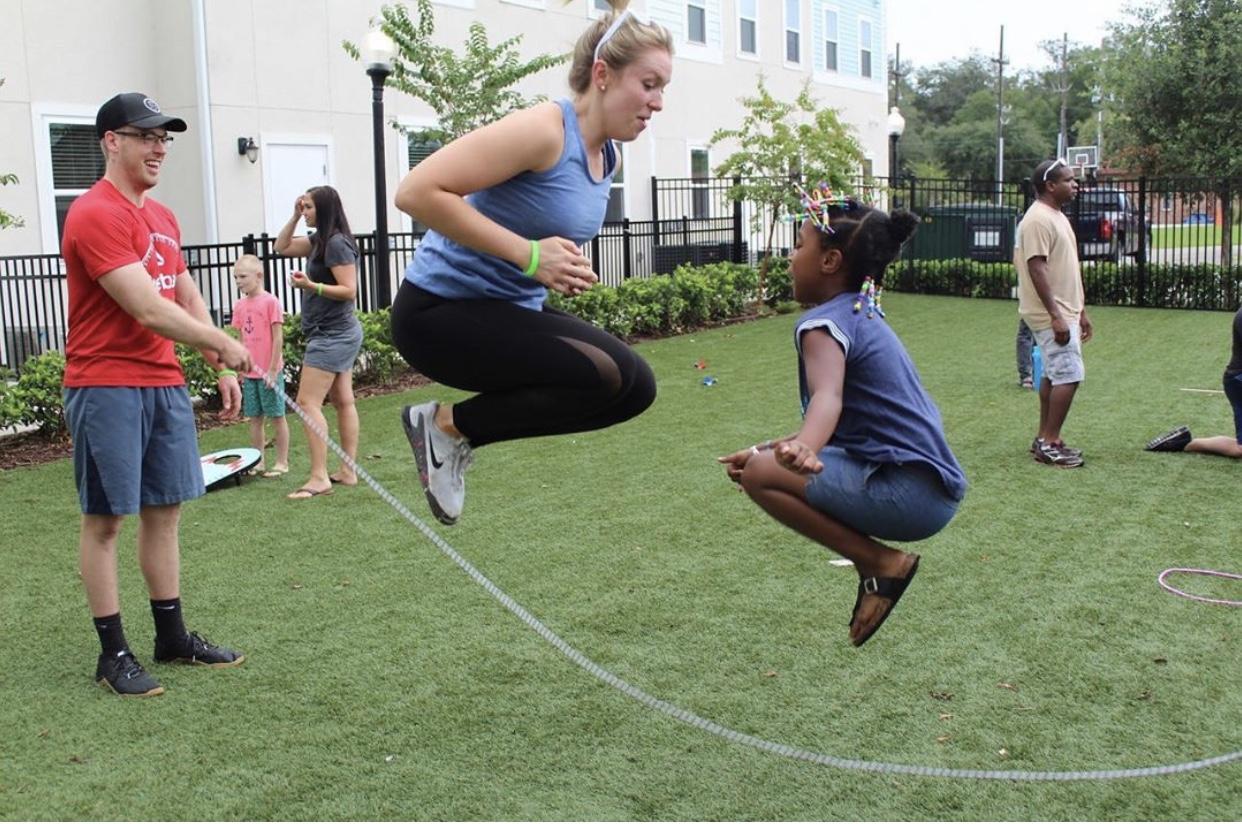 COE volunteer jump roping w child